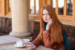 Frau, die Mobiltelefon verwendet und auf jemand Café im im Freien wartet Stockbilder