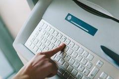 Frau, die moderne ATM-Tastatur verwendet Stockfoto