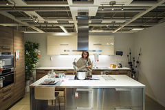 Frau, die moderne Luxusküche kauft Stockbilder