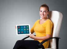 Frau, die moderne Tablette mit bunten Ikonen anhält Stockfotografie