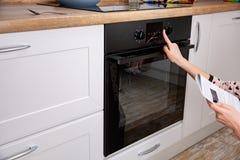 Frau, die Modus auf Ofenplatte kochend sich reguliert stockfotos