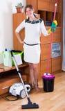 Frau, die Mopp, Staubsauger und das Abwischen im Raum verwendet lizenzfreie stockbilder