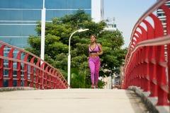 Frau, die am Morgen in der Stadt läuft und ausarbeitet Stockbilder