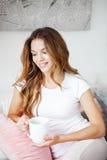Frau, die morgens eine Tasse Tee oder Kaffee im Bett hält Lizenzfreie Stockfotos