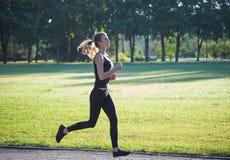 Frau, die morgens Park laufen lässt Lizenzfreie Stockfotos