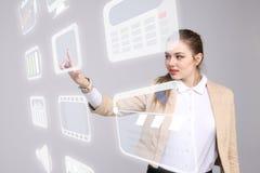 Frau, die Multimedia und Unterhaltungsikonen auf einem virtuellen Hintergrund bedrängt Lizenzfreies Stockbild