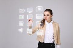 Frau, die Multimedia und Unterhaltungsikonen auf einem virtuellen Hintergrund bedrängt Stockfotos