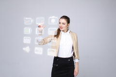 Frau, die Multimedia und Unterhaltungsikonen auf einem virtuellen Hintergrund bedrängt Lizenzfreies Stockfoto