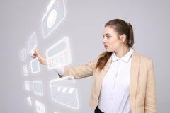Frau, die Multimedia und Unterhaltungsikonen auf einem virtuellen Hintergrund bedrängt Stockfoto
