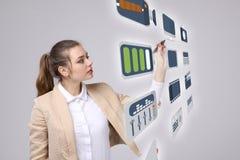 Frau, die Multimedia und Unterhaltungsikonen auf einem virtuellen Hintergrund bedrängt Stockbilder