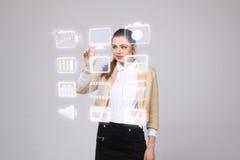Frau, die Multimedia und Unterhaltungsikonen auf einem virtuellen Hintergrund bedrängt Stockbild
