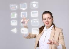Frau, die Multimedia und Unterhaltungsikonen auf einem virtuellen Hintergrund bedrängt Lizenzfreie Stockbilder