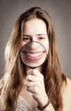 Frau, die Mund durch Lupe zeigt Stockbild