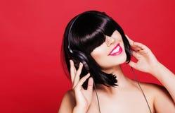 Frau, die Musik auf den Kopfhörern genießen a hört Lizenzfreie Stockfotografie