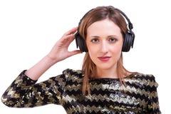 Frau, die Musik auf Kopfhörern hörend steht lizenzfreies stockbild