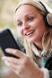Frau, die Musik auf Smartphone hört Lizenzfreie Stockfotos