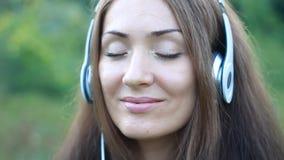Frau, die Musik in den Kopfhörern auf dem im Freien hört Porträt eines schönen Nahaufnahmemädchens stock video footage