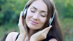 Frau, die Musik in den Kopfhörern auf dem im Freien hört Porträt eines schönen Nahaufnahmemädchens stock footage
