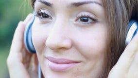 Frau, die Musik in den Kopfhörern auf dem im Freien hört Porträt eines schönen Nahaufnahmemädchens stock video