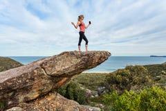 Frau, die Musik hören oder eine Titelliste hoch oben auf einem balancierenden Rock auf Gebirgsrand stockfoto