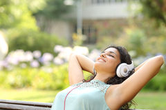 Frau, die Musik hört und in einem Park sich entspannt Lizenzfreie Stockfotografie