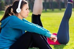 Frau, die Musik mit Smartphone nach Übung hört Stockbild