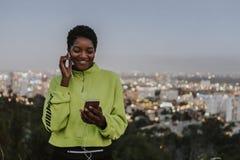 Frau, die Musik von einem Telefon hört lizenzfreie stockbilder