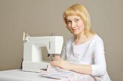 Frau, die Nähmaschine verwendet stockfotografie