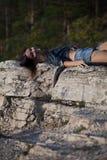 Frau, die nach Felsen liegt lizenzfreie stockfotos