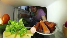 Frau, die nach Lebensmittel im Kühlschrank sucht Die Wahl zwischen Fleisch oder Gemüse stock video
