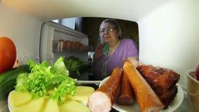 Frau, die nach Lebensmittel im Kühlschrank sucht Die Wahl zwischen Fleisch oder Gemüse stock video footage