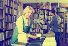 Frau, die nach neuem Buch sucht stockfotografie