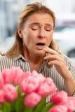 Frau, die nachdem die Blumen niest, die, Allergie haben gerochen worden sind stockfotos