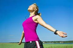 Frau, die nachdem dem Laufen sich entspannt Stockbild