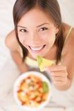 Frau, die Nachos isst Stockbild