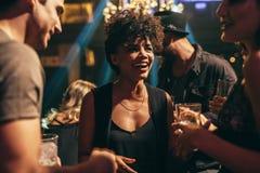 Frau, die am Nachtklub mit Freunden genießt stockfoto