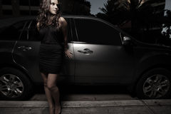 Frau, die nachts durch ein Luxuxsuv aufwirft Stockfotografie