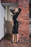 Frau, die nahe Backsteinmauer im Kleid steht Lizenzfreie Stockfotos