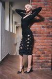 Frau, die nahe Backsteinmauer im Kleid steht Stockfoto