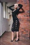 Frau, die nahe Backsteinmauer im Kleid steht Stockfotografie