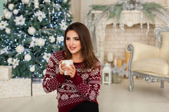 Frau, die nahe Baum des neuen Jahres sitzt stockbilder