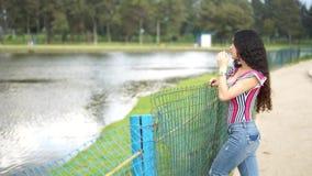 Frau, die nahe bei einem ruhigen See sich entspannt stock video footage