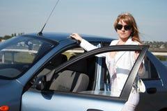 Frau, die nahe blauem Auto steht Stockfotos