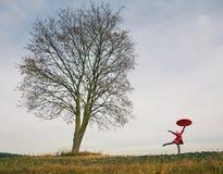 Frau, die nahe dem Baum mit Regenschirm steht Stockfoto