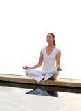 Frau, die nahe dem Meer meditiert stockbild