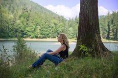 Frau, die nahe dem See sitzt Lizenzfreie Stockfotografie