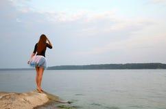 Frau, die nahe dem See wartet Lizenzfreie Stockfotografie