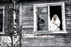 Frau, die nahe der zerbrochenen Fensterscheibe bleibt Stockbilder