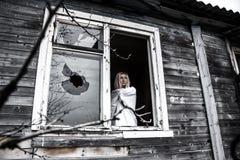 Frau, die nahe der zerbrochenen Fensterscheibe bleibt Stockfotos