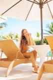 Frau, die nahe einem Swimmingpool sich entspannt Lizenzfreie Stockbilder